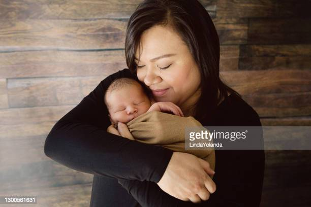mother holding newborn - minority groups stock pictures, royalty-free photos & images