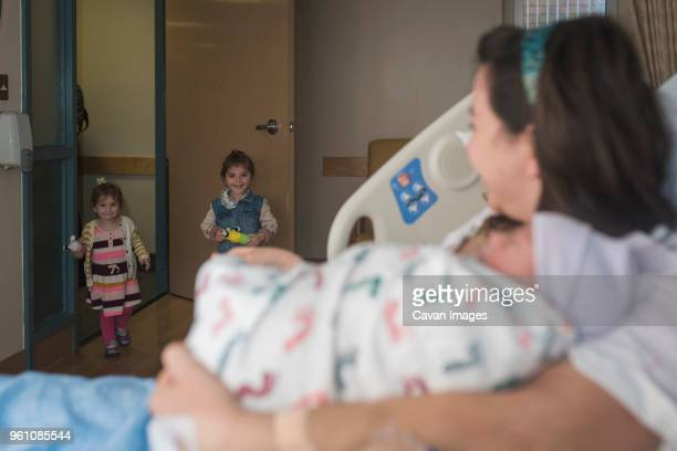 Mother holding newborn son looking at daughters entering in hospital ward while relaxing on bed
