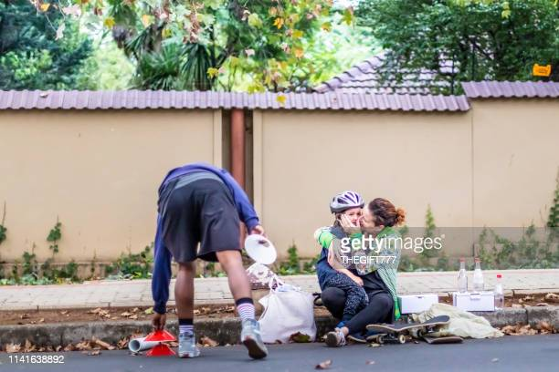 mother holding on to a crying skateboarder child - gauteng province stock pictures, royalty-free photos & images