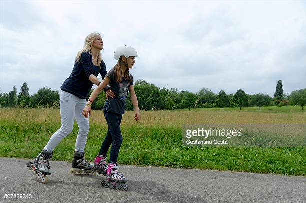 Mother holding onto daughter whilst rollerblading in park
