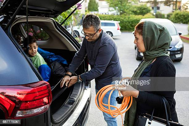 Mother holding pipe while father keeping electric charger by son in car