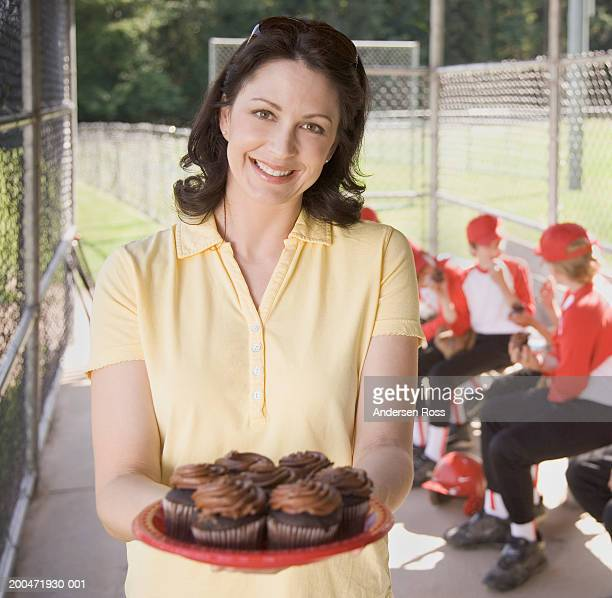 Mother holding plate of cupcakes in baseball dugout