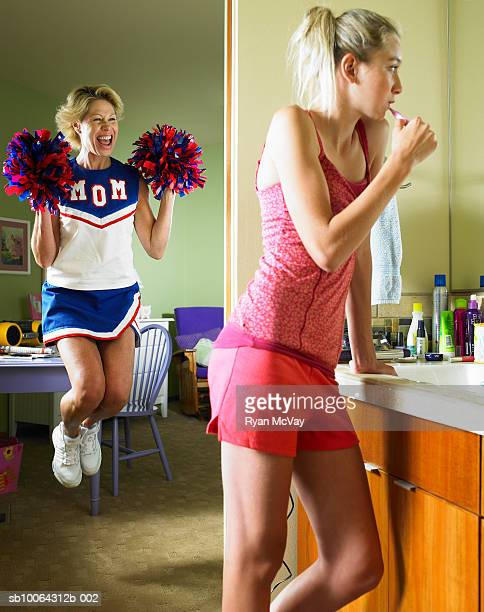 mother holding pom poms and jumping, girl (13-14) brushing teeth in bathroom - teen cheerleader stock photos and pictures