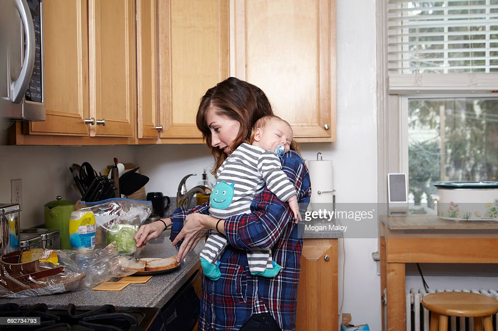 Mother holding sleeping baby boy and preparing sandwich : Stock Photo