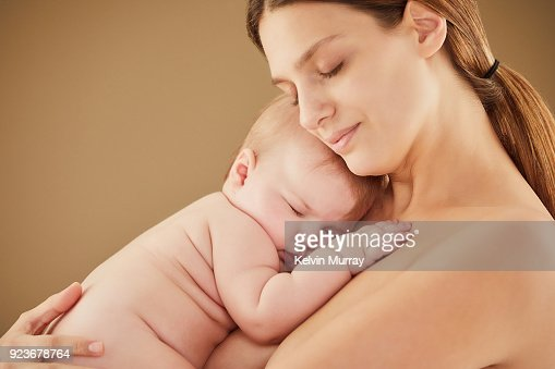 Mother holding sleeping baby girl (5-6 months)