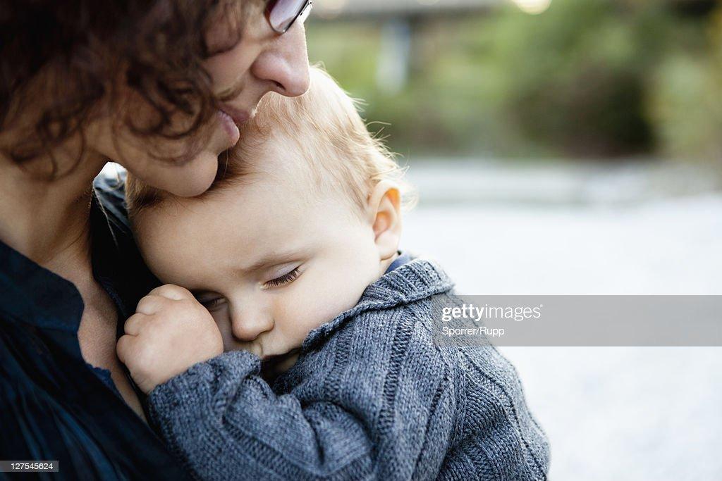 Mother holding sleeping baby : Stock Photo