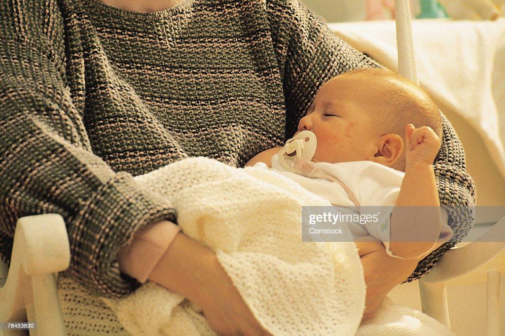 Mother holding sleeping baby : Stockfoto