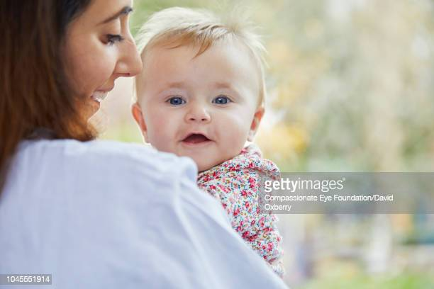 Mother holding smiling baby girl by window