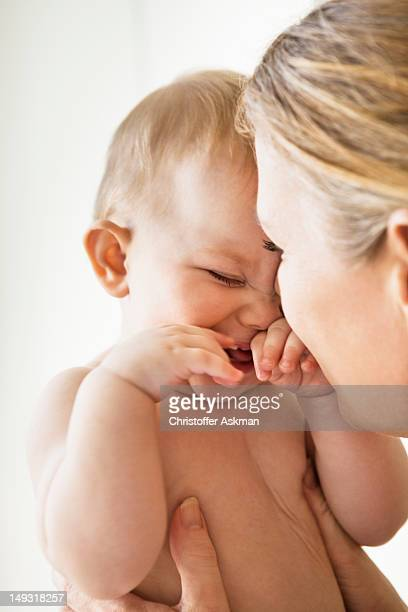 Mother holding smiling baby girl