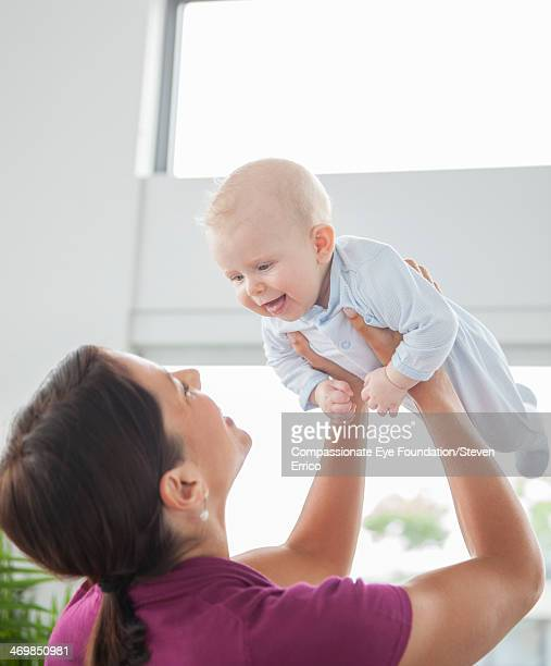 Mother holding smiling baby son