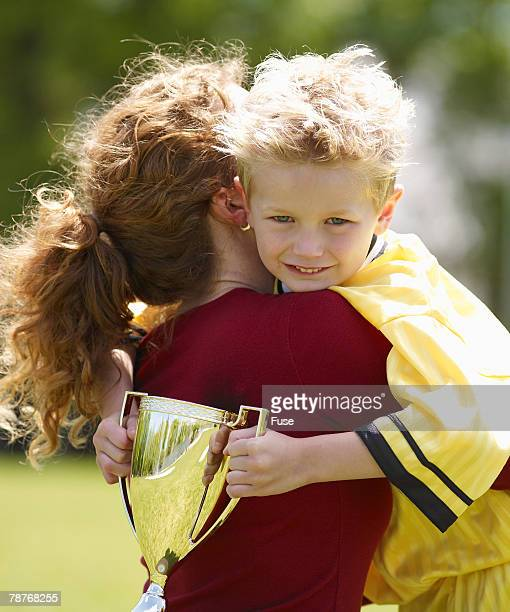 Mother Holding Son After Winning Soccer Game