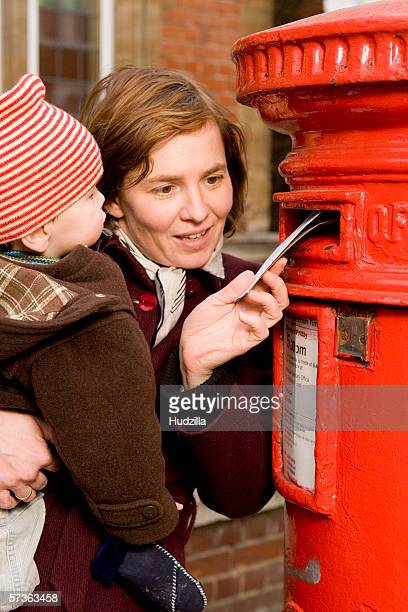 Mother holding son and sending letter, London, England