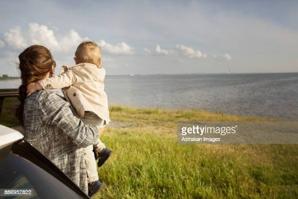 mother holding son (18-23 months) by sea - 18 23 months stock pictures, royalty-free photos & images