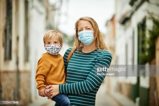 mother holding son in arms on the street with face masks for covid-19 - europa locais geográficos imagens e fotografias de stock
