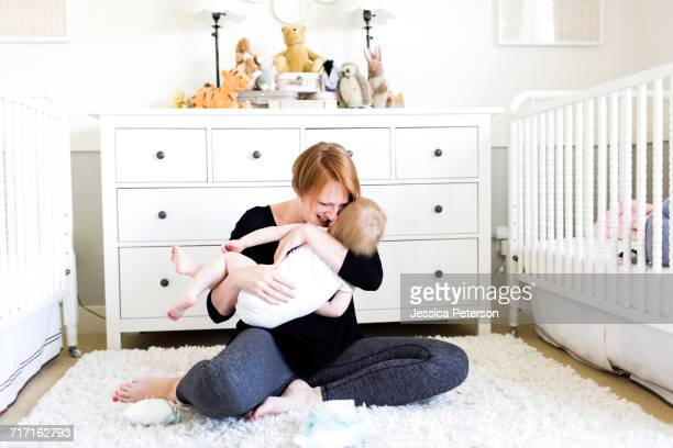 Mother holding son (12-17 months) in nursery