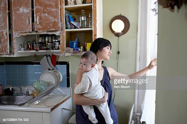 mother holding son (6-11 months) looking out window - 6 11 months stock pictures, royalty-free photos & images