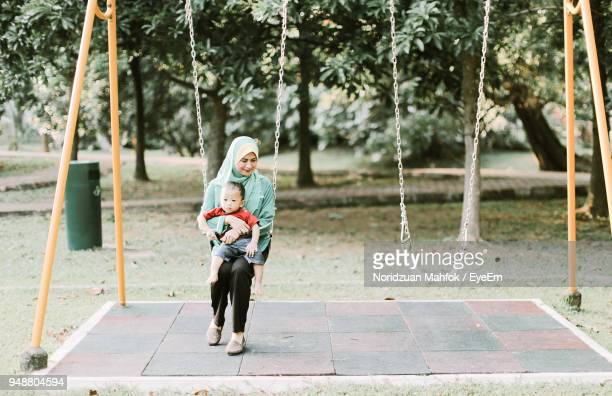 Mother Holding Son While Swinging At Playground