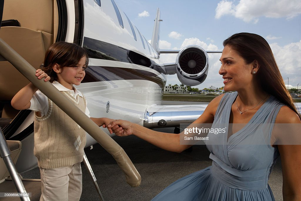 Mother holding son's (3-5) hands on plane steps : Stock Photo