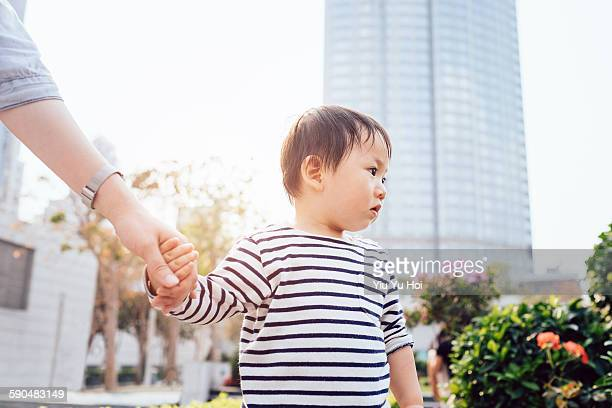 Mother holding the hand of a toddler in the park