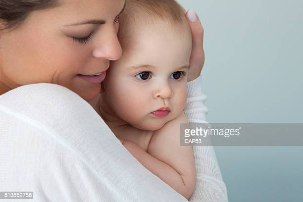 Mother Holding Tight Her Baby Boy On Blue Background