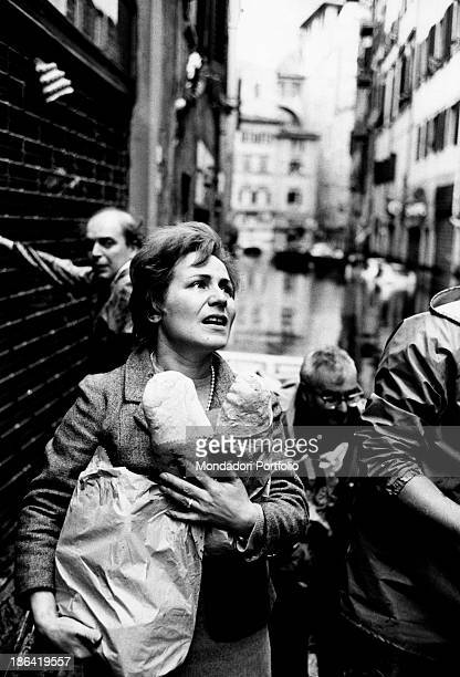 A mother holding tight the food to bring to her relatives struck by the flood of the Arno River Florence November 1966
