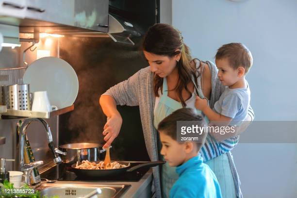 mother holding toddler and cooking, older son standing by - stay at home mother stock pictures, royalty-free photos & images
