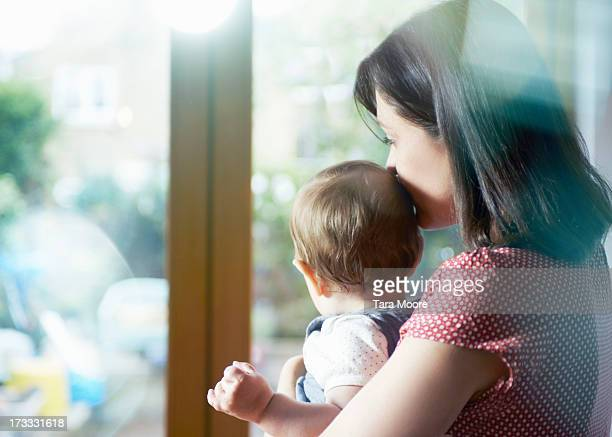 mother holding toddler and looking out window