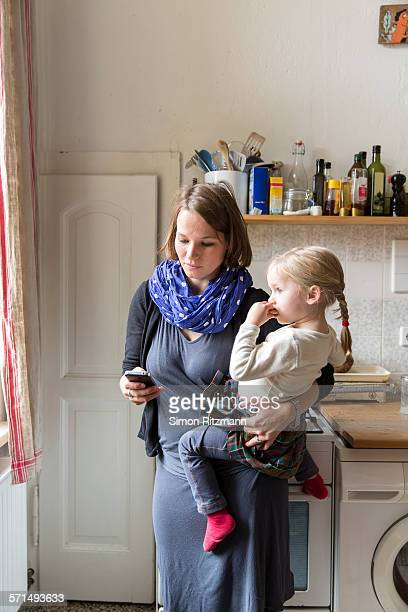 Mother holding toddler girl while using smartphone