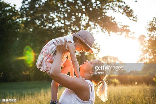 Mother holding toddler in field at sunset