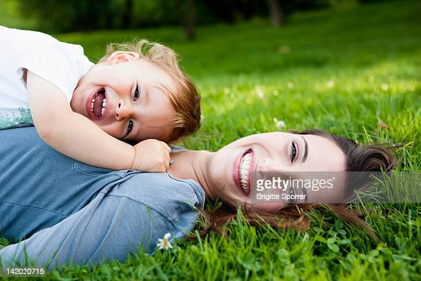 Mother holding toddler in park