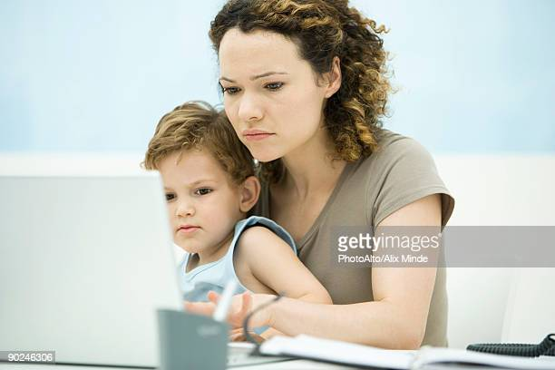 mother holding toddler son in lap while using laptop computer - mom sits on sons lap stock pictures, royalty-free photos & images