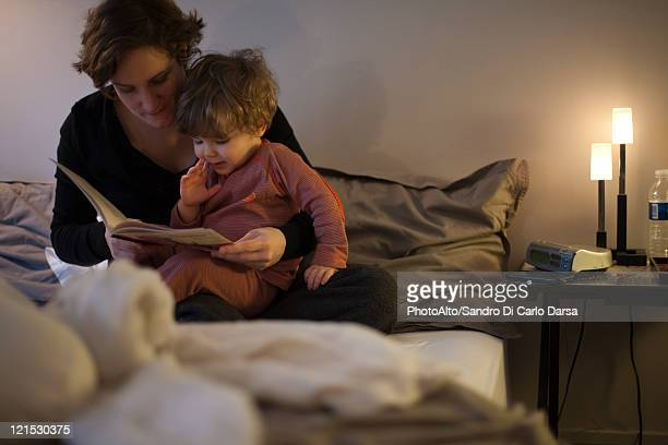 mother holding toddler son on lap, reading bedtime story in bed - storytelling stock pictures, royalty-free photos & images