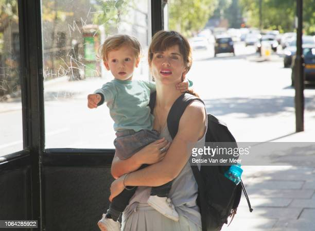 Mother holding toddler while waiting for bus.