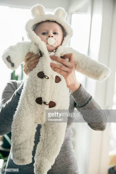 mother holding up baby in a polar bear costume - mama bear stock photos and pictures