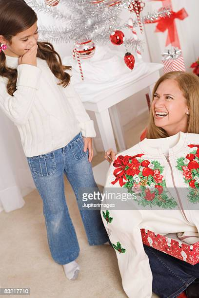 mother holding up sweater she got for christmas with daughter laughing - fille moche photos et images de collection