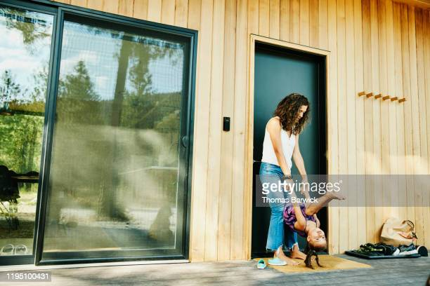 mother holding young daughter upside down while standing on front porch of vacation home - family with one child stock pictures, royalty-free photos & images