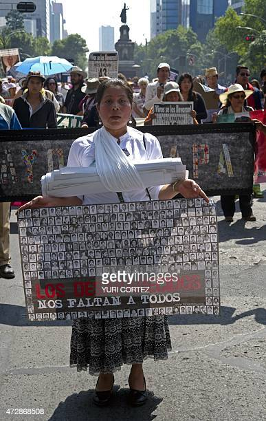 A mother holds a banner with pictures of missing people while taking part in a protest during the Mother's Day commemoration in Mexico City on May 10...