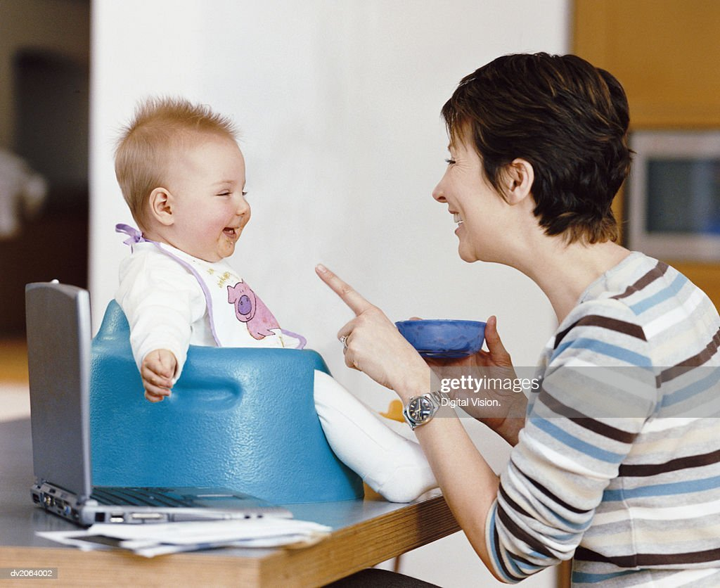 Mother Holds a Bowl of Baby Food, Talking and Smiling at Her Baby in a Highchair : Stock Photo