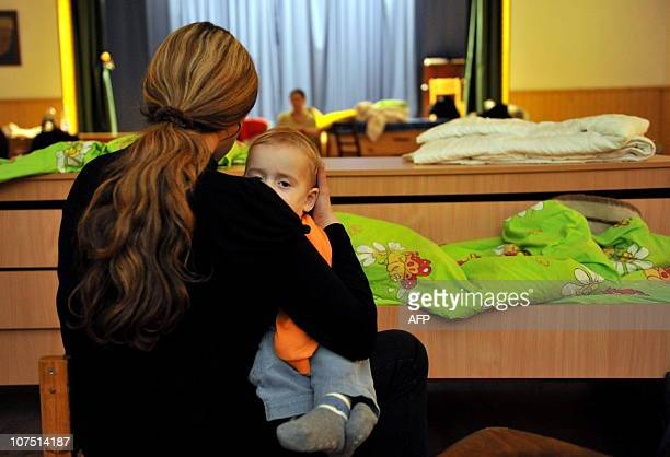 A mother holds a child in her arms as they were evacuated in a local sporthall after heavy snowfalls in Tallinn on December 10 2010 Emergency...