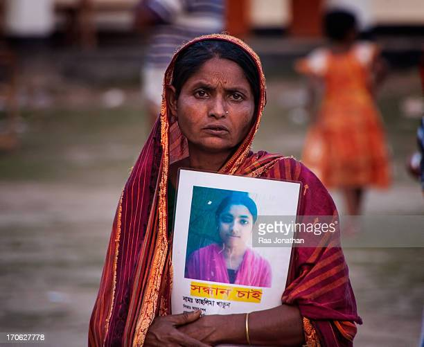 CONTENT] A mother holds a portrait of her missing daughter trapped in the rubble following the collapse of an eightstorey building in Savar on the...