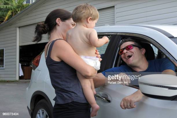 mother holds baby to say goodbye to his father before driving away from home - rafael ben ari bildbanksfoton och bilder