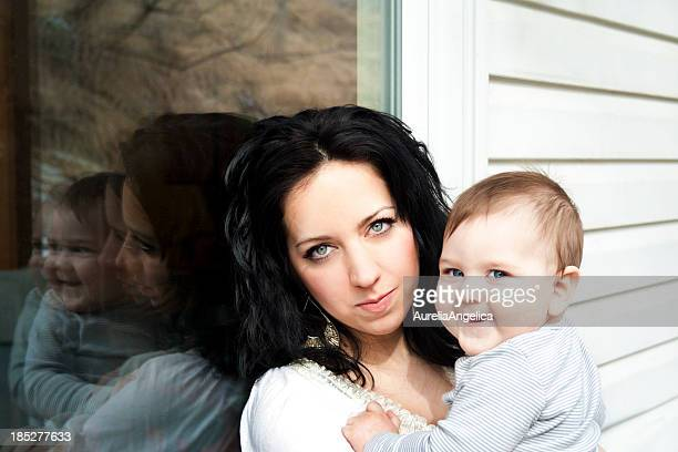 Mother holds baby while leaning against window