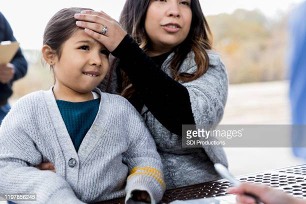 mother holds daughter while describing fever and touching her forehead - selfless stock pictures, royalty-free photos & images