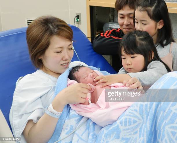 A mother holds her baby born on the first day of Reiwa era while her children and the father look on at a hospital in Izumi city Osaka prefecture on...