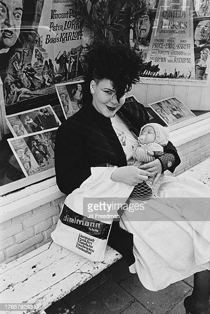 A mother holds her baby outside a cinema in Amsterdam 1982