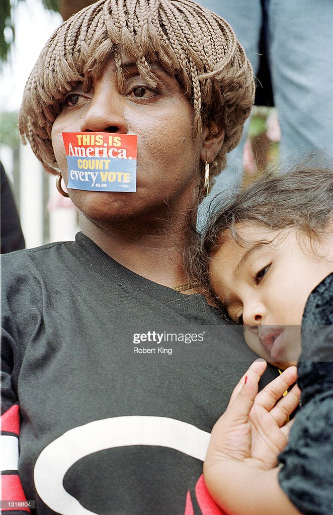 A mother holds her child as hundreds of angry demonstrators take part in a rally on the steps of the old Florida Capitol to protest the U.S. Supreme Court decision to not allow a recount of the Florida undervotes on December 13, 2000 in Tallahassee, Florida.