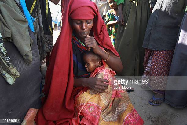 A mother holds her child sick with measles at a camp for Somalis displaced by famine and drought on August 16 2011 in Mogadishu Somalia The US...