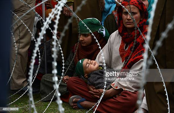 A mother holds her sleeping child during a campaign rally by Kashmir's main proIndia opposition People's Democratic Party addressed by party patron...