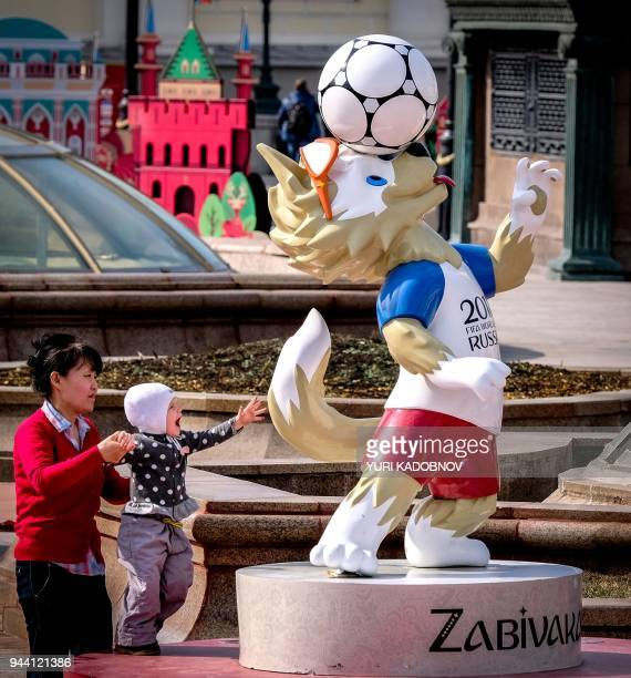 A mother holds her son as he touches a statue of Zabivaka the official mascot for the 2018 FIFA World Cup in Manezhnaya square in downtown Moscow on...