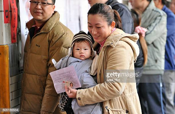Mother holds her son as she queues to cast her vote outside a polling station at the Xindian district in the New Taipei City on January 16, 2016....